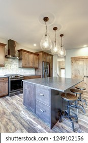 Luxurious open plan kitchen design with large center island, granite counter tops and stainless steel appliances.