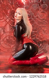 luxurious plus size curvy blonde dressed in black latex rubber clothes and posing in the red smoke alone