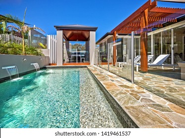 Luxurious pool with tiled passage and glass boundary