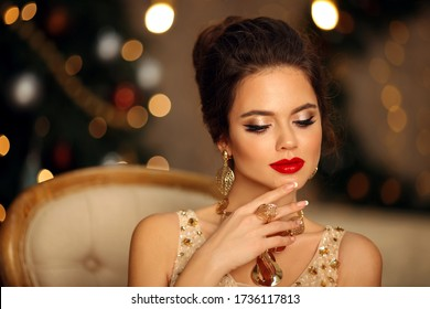 Luxurious portrait of elegant woman with wedding hairstyle and makeup. Beautiful brunette girl with golden jewelry in prom dress sitting on modern chair over bokeh lights xmas decorations.