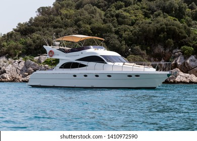 A luxurious powerboat cruising through beautiful blue waters.Side View