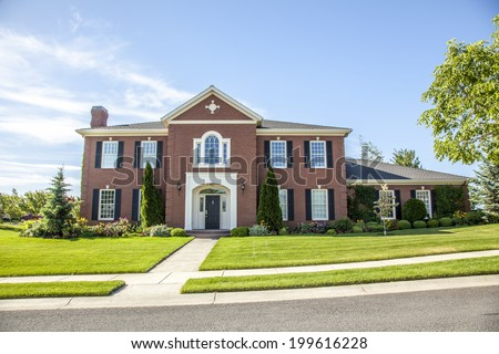 luxurious red brick house with green lawn