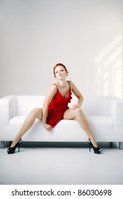 Luxurious redhead woman in a red dress on white couch