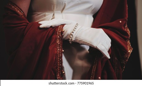 Luxurious retro woman with expensive jewelry in white and red historical 18th century dress posing. Girl in long silk gloves.