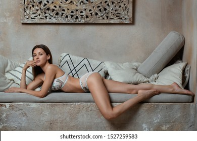 Luxurious rich brown hair woman posing laying in lingerie panties with long naked barefoot legs on stone bench with pillows in desert Arabic or exotic Asian tropical style interior spa house or home