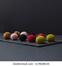 A luxurious set of chocolate candy truffles, round chocolate candies, on a stone stand on a black background, with raspberries, with nuts, with waffle chips, black cocoa, alkalized cocoa, matcha tea