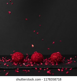 A luxurious set of chocolate truffle chocolates, round chocolate candy, on a stone stand on a black background,  raspberries