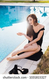luxurious sexy woman in a black dress posing by the blue pool, enjoying a rich life and relaxing