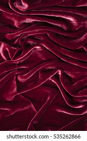 luxurious and soft waves of bloody red velvet background. Texture of bloody red velour background
