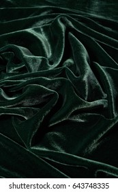 Luxurious and soft waves of green velvet background. Texture of green velour background
