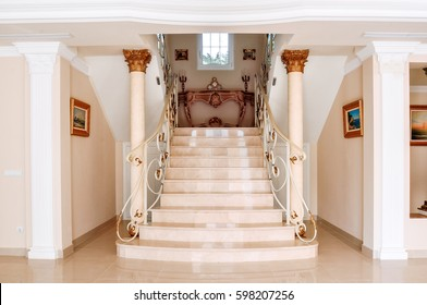 Luxurious Staircase With Marble Steps And Decorative And Ornamental Iron  Railings. On The Top Are