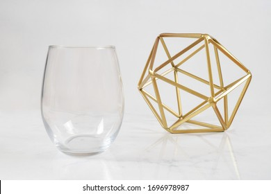 A luxurious stemless wine glass chills on a white marble background next to a modern gold sculpture. Plenty of copy space to add your own design to the no stem wineglass