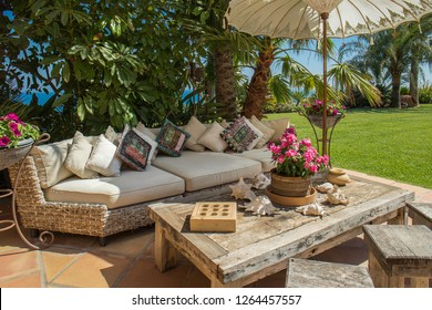 Luxurious summer or rest home with comfortable sofa and cushions in front of the pool with a lovely garden