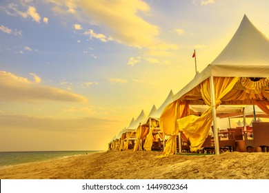 Luxurious tents at desert beach camp, Inland Sea, Khor al Udaid in Persian Gulf, southern Qatar. Scenic sunset sky in Middle East, Arabian Peninsula.Inland sea is a major tourist destination for Qatar