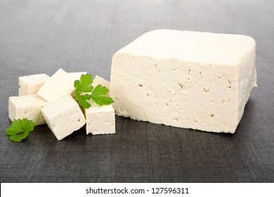 Luxurious tofu background. Tofu piece, cubes and fresh parsley isolated on dark background. Culinary vegan and vegetarian eating.