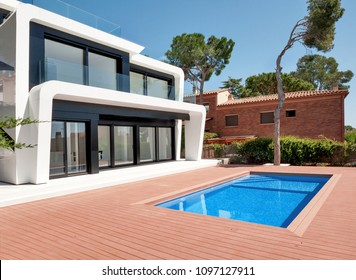 Luxurious villa with swimming pool at dusk. External view of a contemporary house. New technologies in construction.