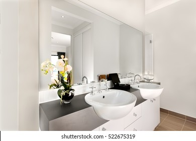 Luxurious washroom included two shiny white washstand made of ceramic, there are silver and curved faucet fixed to sink. The taps can give warm water.