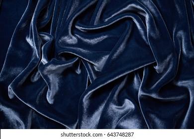 Luxurious waves of dark blue velvet background. Texture dark blue velour background