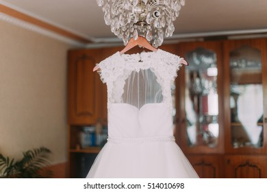 Luxurious wedding dress hanging on luster at dressing room