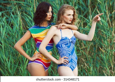 Luxurious weekend concept. Portrait of two gorgeous women (girlfriends) in trendy colorful swimsuits posing on beach. Disco (70s vintage) style. Arty waterproof make-up. Sunny summer day. Outdoor shot