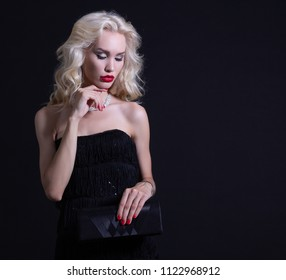 Luxurious woman with bright lips with a purse in hands on black background.