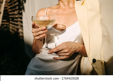 Luxurious woman wearing a white dress, holding a coupe with champagne in sun light. Concept of an open air party.