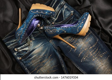 Luxurious women's denim shoes in rhinestones and jeans in rhinestones on a black silk. Fashion background. Top view