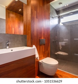 Luxurious wooden bathroom with shower, countertop basin, mirror and toilet