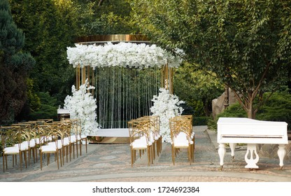 Luxurious yellow-gold wedding arch decorated with white flowers in nature among the trees. wedding ceremony. white piano on the nature. chairs for guests on the street.