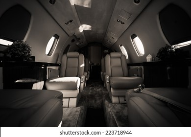 a luxury aircraft interior, leather seats, poor light