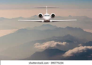 Luxury Airplane fly over clouds and Alps mountain on sunset. Front view of a big passenger or cargo aircraft, business jet, airline. Travel concept. Empty space for text
