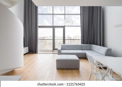 Luxury apartment with window wall, gray sofa and white table