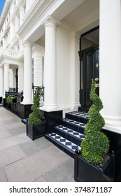 Luxury Apartments. White Facades of Luxury Houses with green plants in front. London, UK