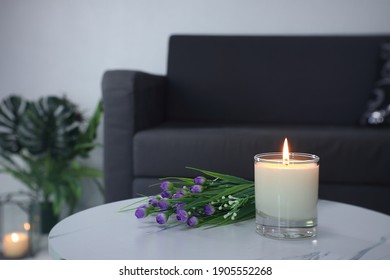 luxury aroma lighting aromatic scented candle glass displayed on the white marble table with bouquet of flowers to creat romantic and relax ambient with background of grey sofa in living room - Shutterstock ID 1905552268