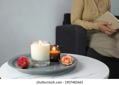luxury aroma lighting aromatic scented candle glass displayed on white marble table with rose flowers to creat relax ambient with background of a woman sitting and reading on grey sofa in living room - Shutterstock ID 1907482465