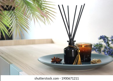 luxury aroma scent reed diffuser glass bottle is on the wooden table and amber glass of scented candle to creat romantic and relax ambient in the bedroom in the morning on happy valentine day