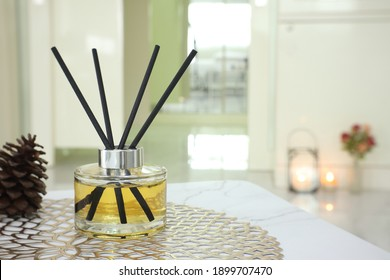 luxury aromatic scent of reed diffuser glass bottle is used as room freshener on the marble table with scented candle in the bedroom with background of the light from the window in the morning