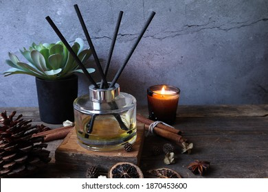 luxury aromatic scented reed diffuser or air freshener decorated on wooden table with background of scented candle in the living room of the house during Christmas new year party celebration