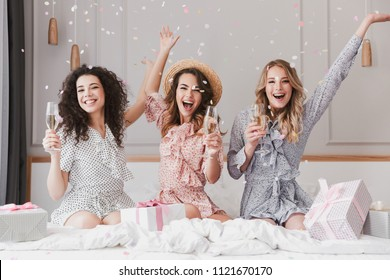 Luxury bachelorette party in posh apartment while happy young three women 20s having fun and drinking champagne under falling confetti