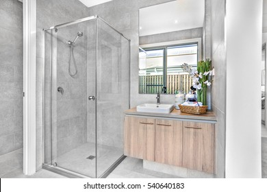 Luxury bathroom closeup with the shower and washing area, room is illuminated from sunlight and yellow light from the ceiling, colorful area.