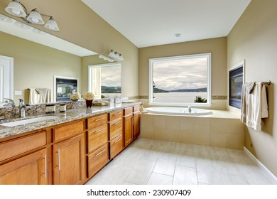 Luxury bathroom with fireplace and bay view.  Brown vanity cabinet with granite top and mirror