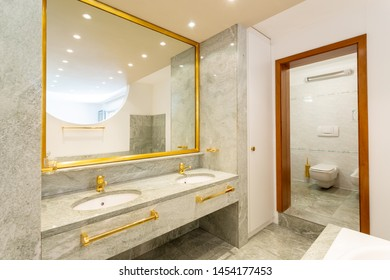 Luxury bathroom with green marble and gold sinks. Nobody inside
