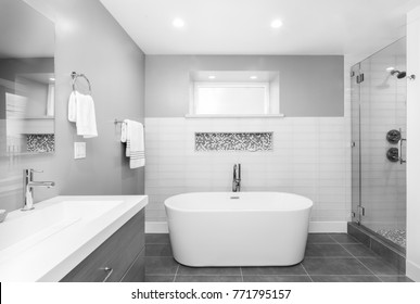 Luxury bathroom interior with an oval bathtub black stone tiles and with glass shower in black and white