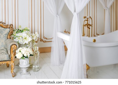 Luxury bathroom in light colors with golden furniture details and canopy. Elegant classic interior.