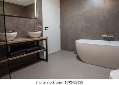Luxury bathroom with polished concrete on the walls and PVC on the floor - Shutterstock ID 1392422615