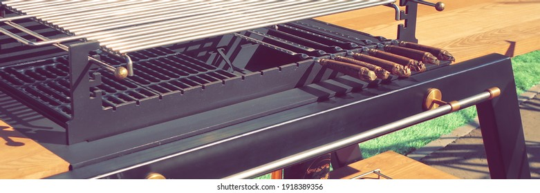 luxury BBQ Grill Appliance. Outdoor Backyard Kitchen Table With BBQ Charcoal Grill Appliance. Family Garden Party Barbecue Grill, Closeup View, Green Backyard Lawn In The Background.