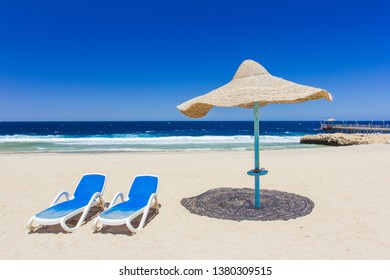 luxury beach Egypt against the background of the beauty of the sea with coral reefs. Sunny resort beach with umbrella and beach chairs at the shore of Red Sea in Hurghada, Egypt, Africa in summer hot