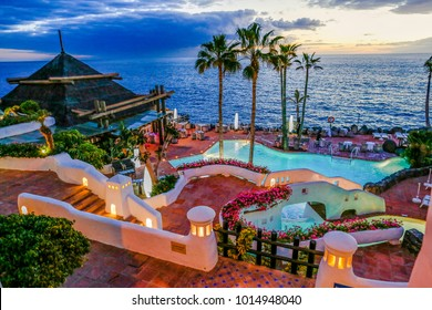 Luxury beach resort, bungalow near endless pool over sea sunset, evening on tropical island with beautiful magic sky
