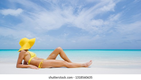 Luxury beach travel - Sexy woman sunbathing on the beach with bikini beach body. Beautiful multiracial Asian Caucasian female model on travel vacation holidays.