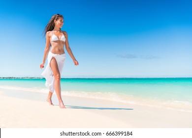 Luxury beach travel vacation swimwear woman relaxing walking on white sand in beachwear cover-up